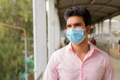 Face of young Indian businessman with mask thinking at the footbridge