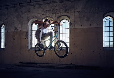 The BMX rider jumps with a bicycle.