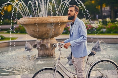 A man on a bicycle over fountain background.