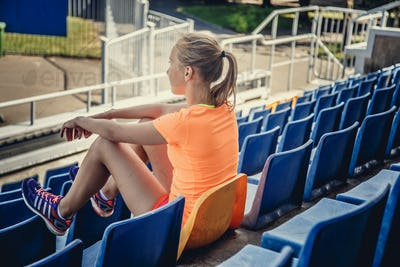 Blond female sitting on plastic seat.