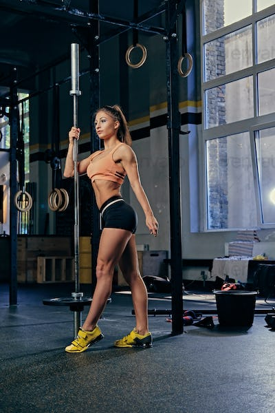 Female model holds barbell over trx straps stand in a gym.