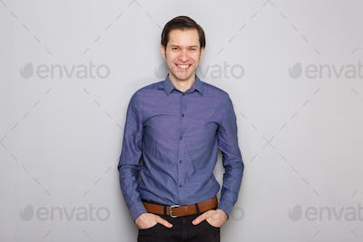 handsome young businessman standing by gray wall smiling