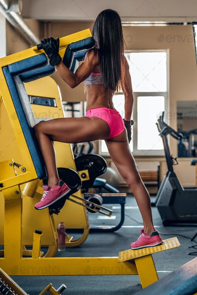 Female doing workouts on legs exercising machine.