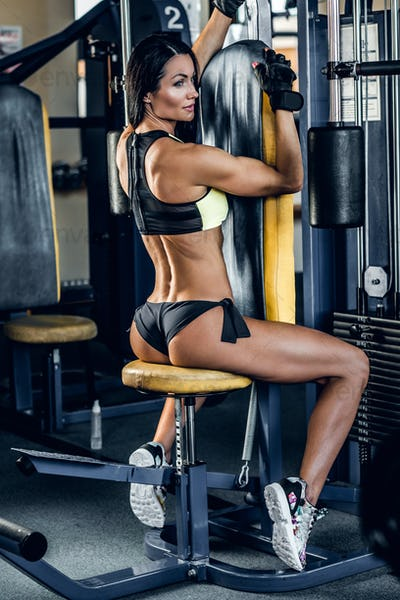 Brunette  female from the back doing workout on exercising machine.
