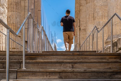 Athens Greece. Young man leaving Acropolis, wooden stairs and covid 19 protective measures