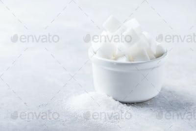 Sugar cubes and grain of sugar