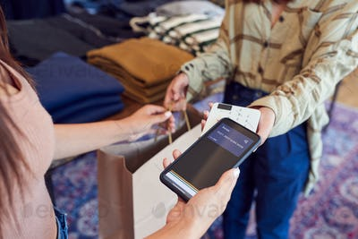 Woman In Clothing Store Making Contactless Payment With App On Mobile Phone
