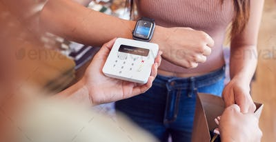 Woman In Clothing Store Making Contactless Payment With Smart Watch At Sales Desk