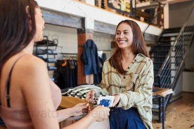 Woman In Clothing Store Making Contactless Payment At Sales Desk Holding Credit Card To Reader