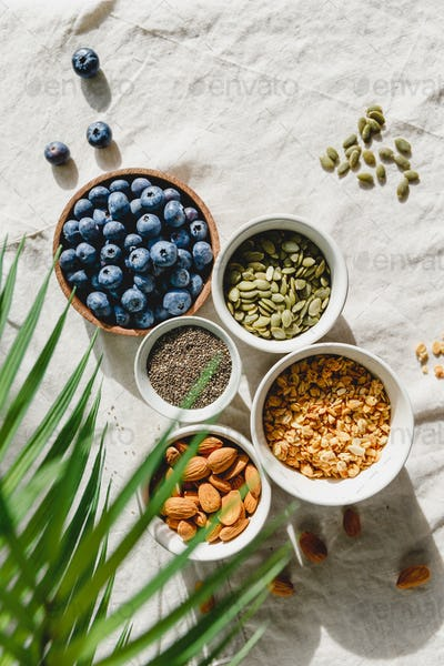 Top view of breakfast ingredients like cereal, almond, blueberry, pepitas and chia seeds