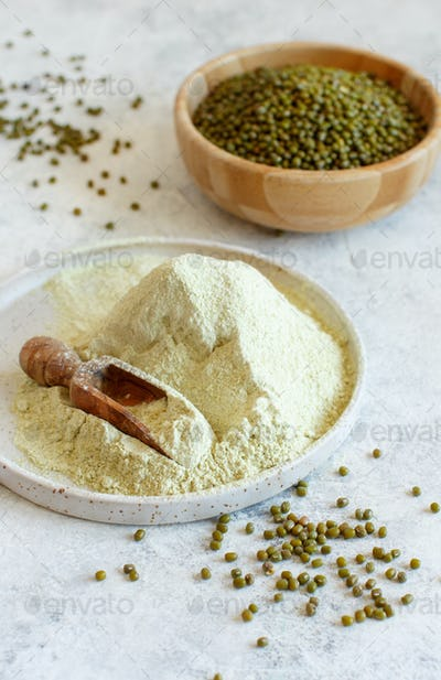 Mung beans flour and grain with a wooden spoon