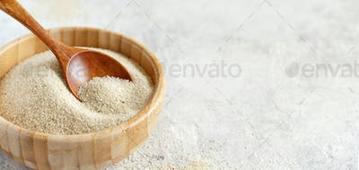 Raw fonio seeds in a bowl with a spoon