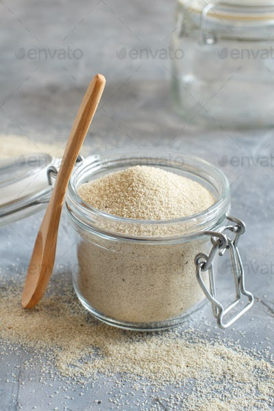 Raw uncooked fonio seeds in a glass jar with a spoon