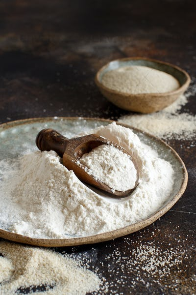 Raw fonio flour and seeds with a spoon on dark background