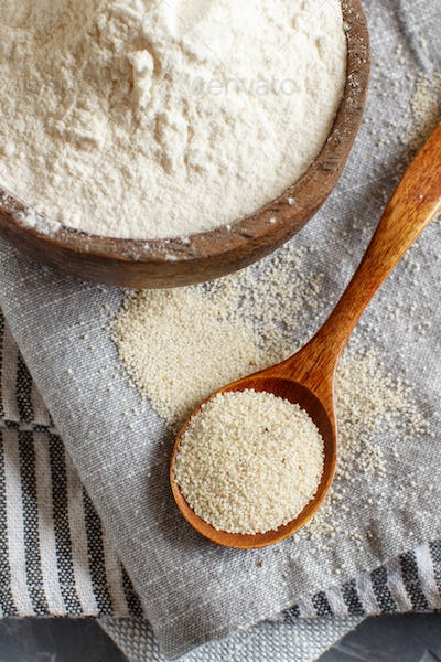 Raw fonio flour and seeds with a spoon on grey napkins