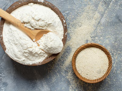 Raw fonio flour and seeds with a spoon on grey background