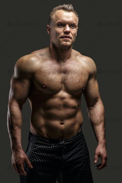 Muscular man posing in studio on grey background