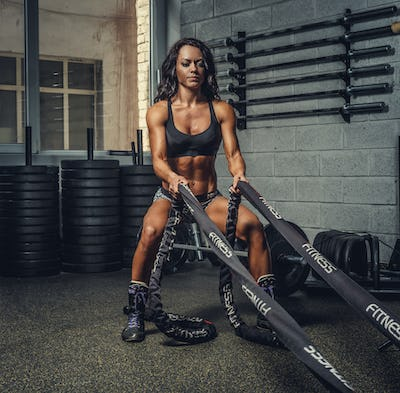 Female fitness model exercising with battle rope.