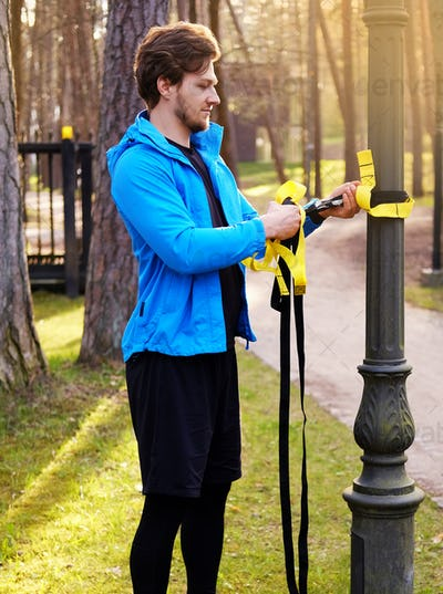 A man exercising in a park with trx fitness strips.