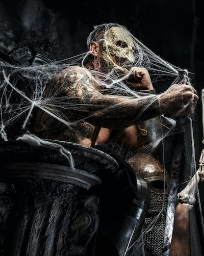 Muscular man with skull on his face.