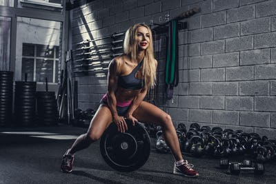 Blond female with barbell weight.