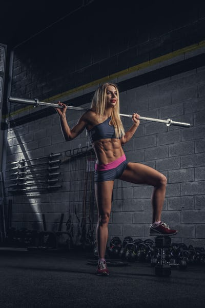 Blond sporty female with barbell.
