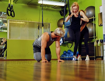 Male and two females doing trx straps exercises in a gym club.