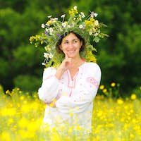 Smiling woman in national clothing and wreath standing in meadow