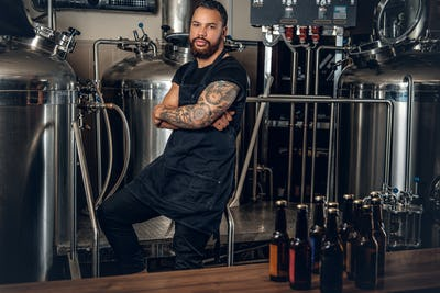 Black man manufacturer presenting craft beer in the microbrewery.