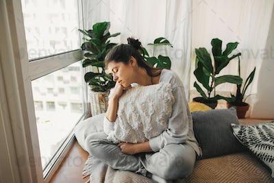 Sad hipster girl holding pillow, sitting at home during quarantine