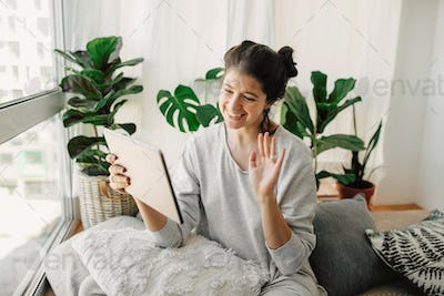 Happy hipster girl chatting on tablet, communicating live with family  from home