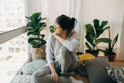 Sad hipster girl sitting at home during quarantine and looking at window