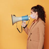 Side view of young brunette woman in protective mask speaknig in megaphone