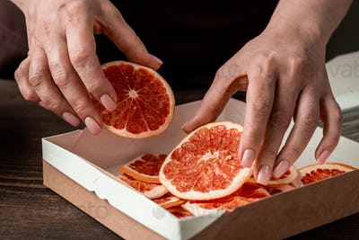 Hands of woman putting homemade dried orange or grapefruit slices into box
