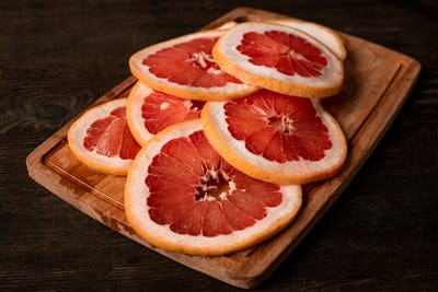 Pile of sliced fresh grapefruit on wooden board ready to be put in fruit dryer