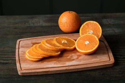 Group of fresh orange slices and halves of the fruits on wooden chopping board