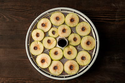 Flat layout of circle tray of fruit dryer with slices of fresh apples on table