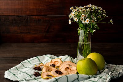 Fresh granny smith apples, vase with garden flowers, dry fruit and star anise