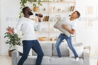 Cheerful black dad and preteen son having fun together in living room