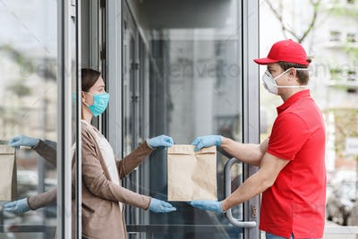 Courier in medical mask and gloves transfers package to customer at home