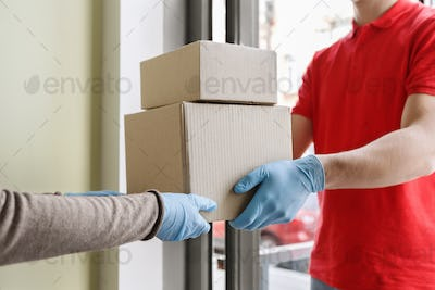 Safe delivery concept. Courier gives boxes to client in mask and gloves