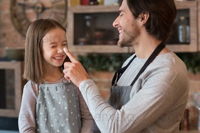Loving Young Dad Playing With His Little Daughter In Kitchen, Fooling Together