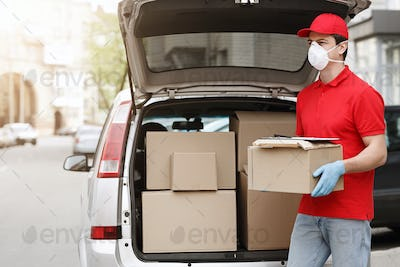 Delivery man with protective mask and gloves holds box near open car with many packages