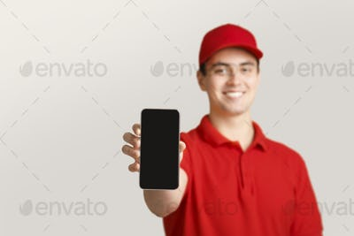 Modern post and online application. Deliveryman shows smartphone with blank screen