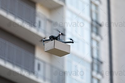 Flying electric drone with small package. Copy space