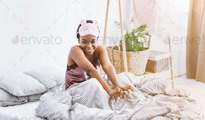 Cute african american girl in soft mask for sleeping, sits in bed