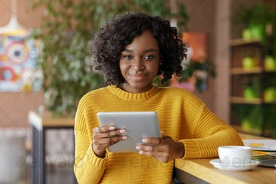 Attractive african woman using digital tablet during coffee break