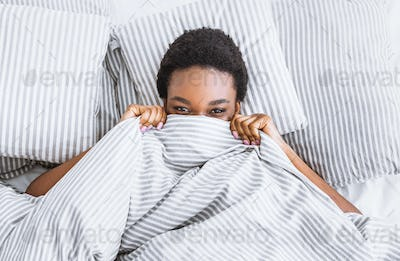 Woman covers her face with blanket, lying in bed