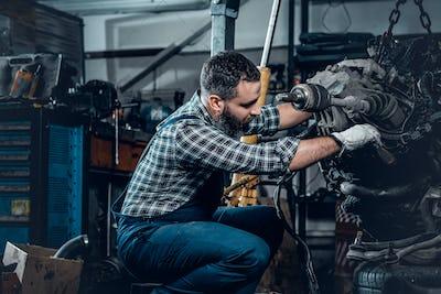 Bearded mechanic repairing car's engine.