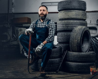 A man sits on a tire.